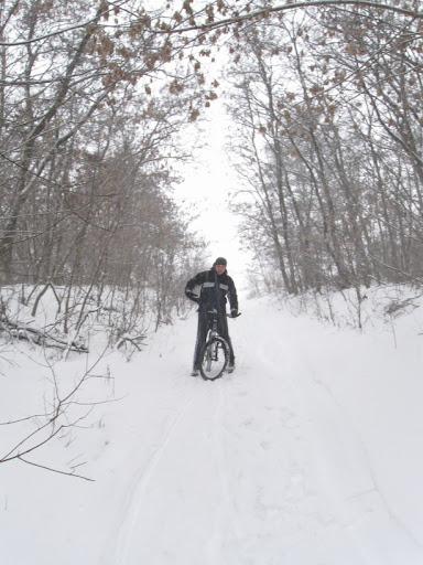 по снегу в лесу на велосипеде