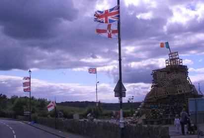 Britische Fahnen und die irische Fahne auf einer Paletten-Pyramide zur Siegesfeier der Oranier am 12. Juli, Nordirland