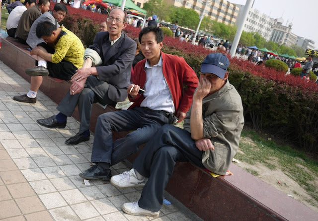 three men sitting at Nanmen Square in Yinchuan, Ningxia, China