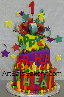 Three tier mad hatter yellow, purple and red kid's 1st birthday cake with stars, diamonds, stripes, and sugar bow.