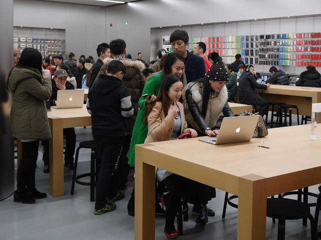 three young women in front of a laptop at Jiefangbei Apple Store in Chongqing on opening day