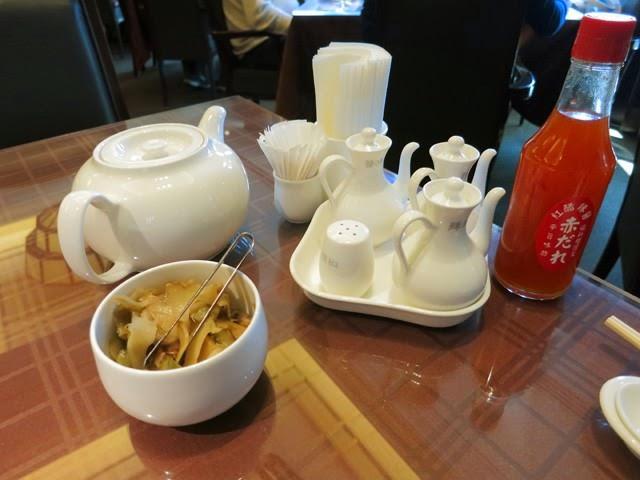 卓上に置かれた食べ放題のザーサイと烏龍茶、卓上調味料類