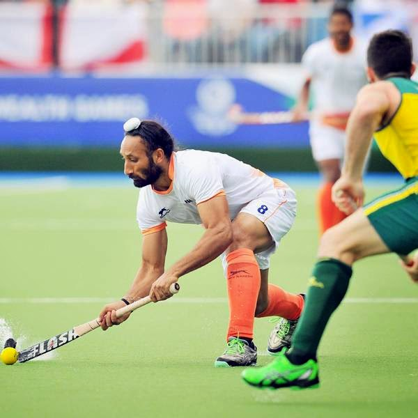 India's Sardar Singh (L) passes the ball past Australia's Trent Mitton (R) during a men's field hockey match between India and Australia at the Glasgow National Hockey Centre at the 2014 Commonwealth Games, in Glasgow, on July 29, 2014.