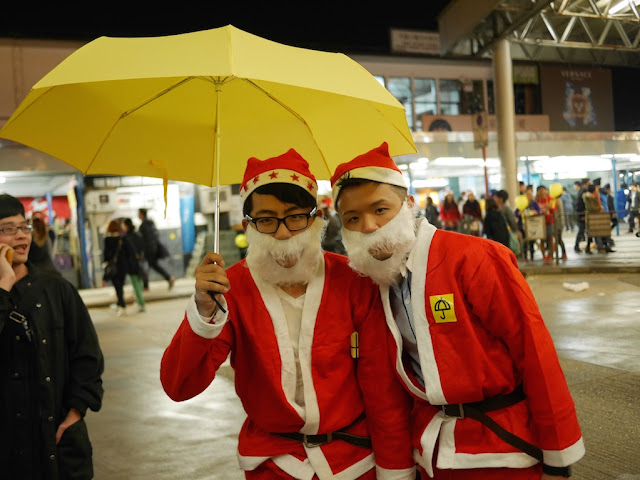 two young men wearing Santa outfits standing under a yellow umbrella