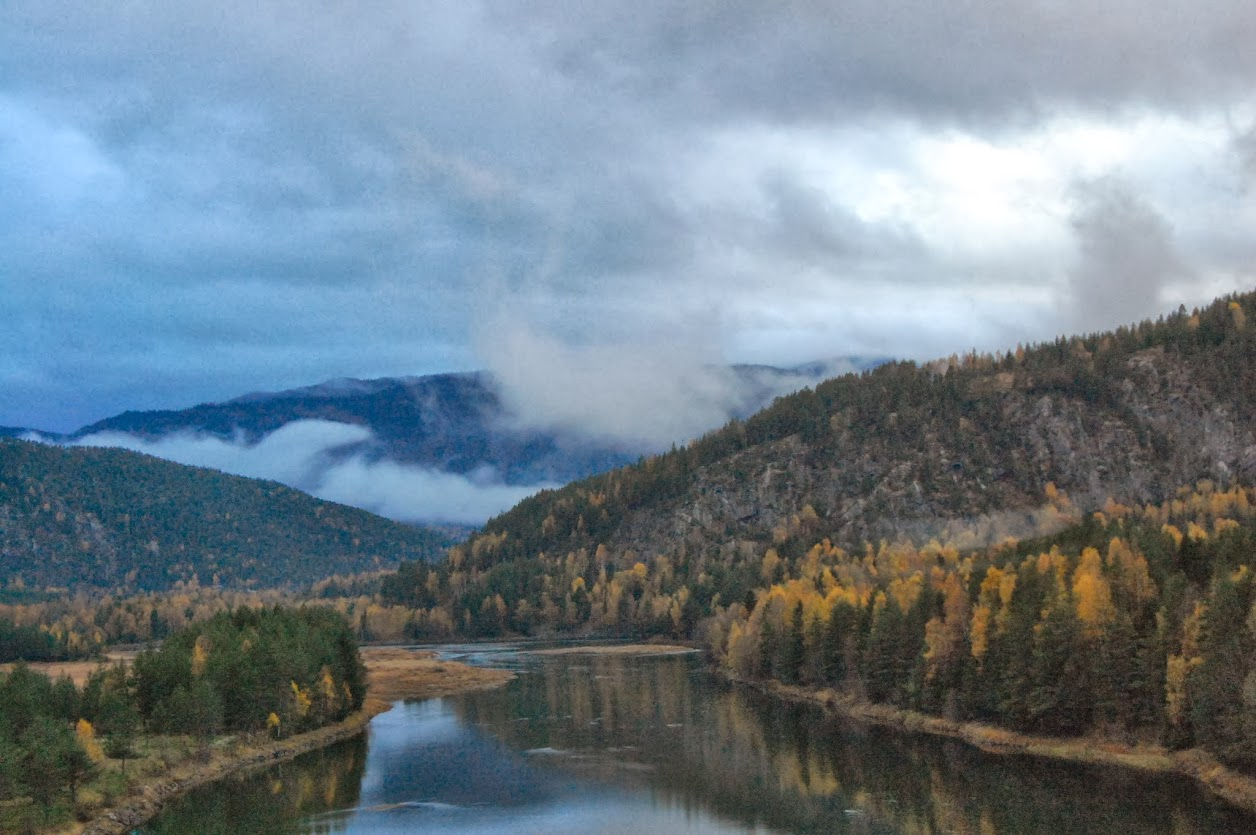 A river running through mountains with fall foliage and low hanging clouds.