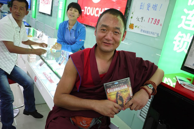 Tibetan monk holding a DVD of the movie Colombiana in Xining, Qinghai, China