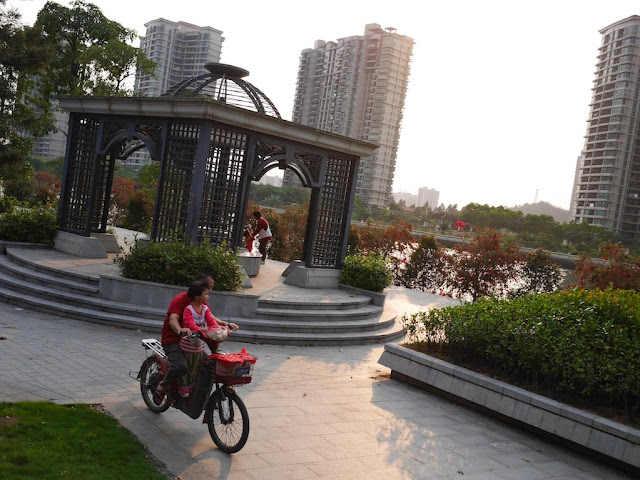 man with a young girl riding a motorbike through a riverside park