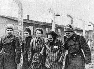 Befreite Häftlinge mit Sowjetsoldaten vor Baracken und Stacheldraht.