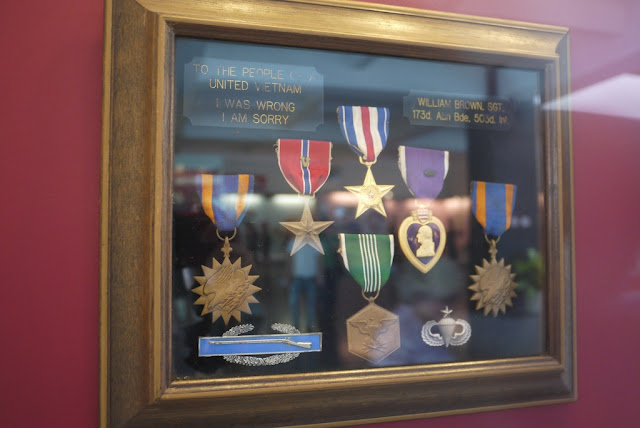 "various medals with a plaque reading ""To the people of a united Vietnam: I was wrong. I am sorry."""