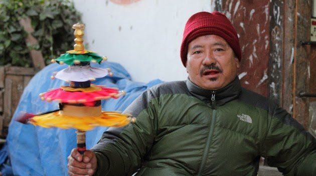 Local Trongsa Man with a colorful prayer wheel
