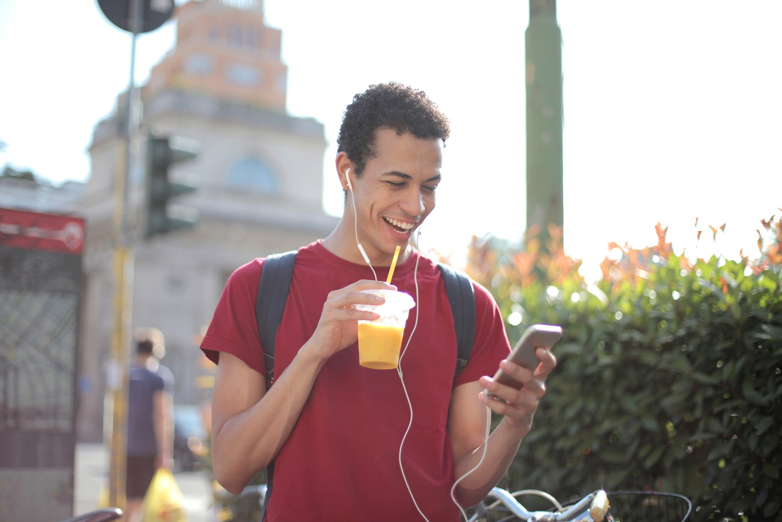 a young man drinking orange juice and listening to music while looking at his cell phone
