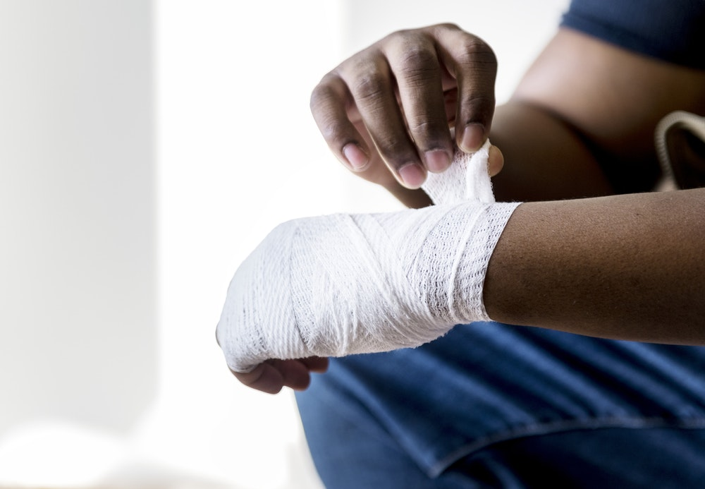 person wrapping hand with adhesive bandage