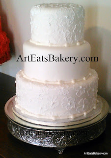 Three tier round white fondant wedding cake with elegant romantic brush embroidery flowers and sugar pearls