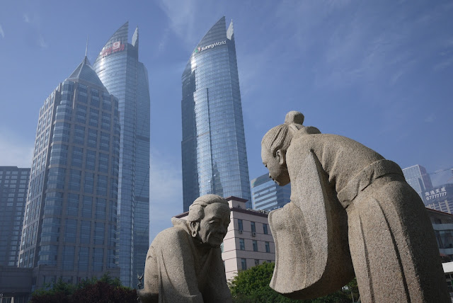 sculpture of traditional scene in front of modern skyscrapers