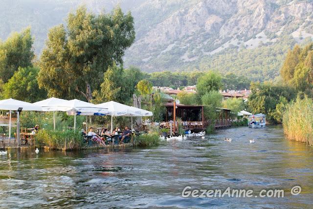 azmak kenarındaki çay bahçeleri, restoranlar, azmakta yüzen ördekler, arkada yüksek dağlar, Akyaka
