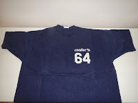 Photo of the front of a Confer % 64 t-shirt