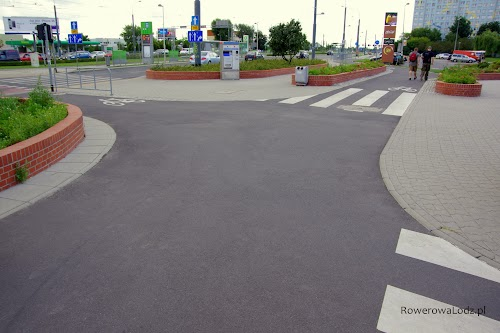 Łagodne łuki na asfaltowym skrzyżowaniu dwóch dróg dla rowerów.