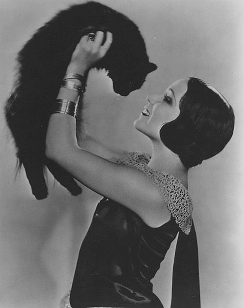 Dolores Del Rio holding up a cat
