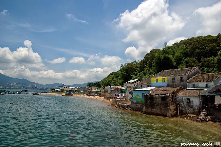 島上古樸的石屋被漆上色彩(左遠方是深圳鹽田貨櫃碼頭)