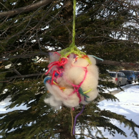 Crocheted net stuffed with yarn, wool and alpaca roving for the birds