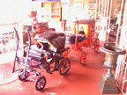 a couple of scale model childrens carriages in window display