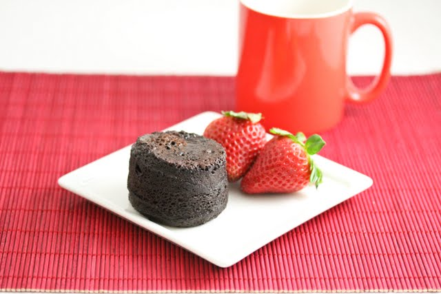 photo of a flourless chocolate cake on a plate with strawberries and a mug in the background