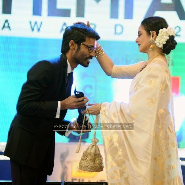 Rekha presents the Critics Best Actor Award to Dhanush for his performance in the Tamil film 'Mariyan' during the 61st Idea Filmfare Awards South, held at Jawaharlal Nehru Stadium in Chennai, on July 12, 2014.