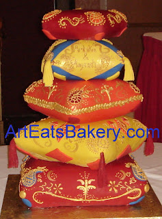5 tier custom pillows red, yellow, blue, and orange fonant wedding cake with gold and copper Mendi designs