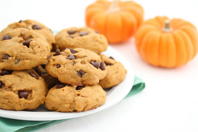 photo of a plate of Pumpkin Chocolate Chip Cookies with two small pumpkins in the background