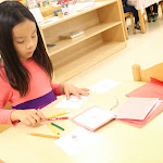 This third-year primary girl is making a booklet about the parts of a flower. As students progress from just assembling puzzles, to tracing and coloring them, to making booklets, they really absorb scientific terminology at an early age.