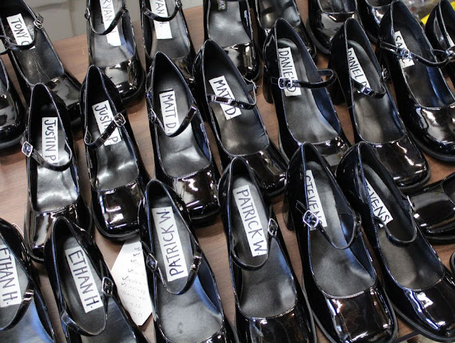 a dozen pairs of large patent-leather high-heeled shoes with men's names written inside them