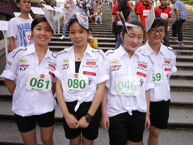 participants in the Macau tray race wearing cutouts of racing scenes on their heads