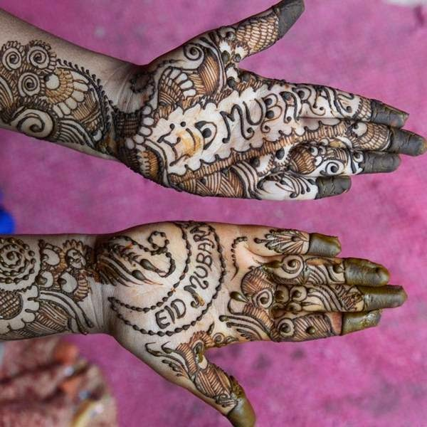 A customer displays her hands styled with mehendi (henna) during Chand Raat or Night of the Moon, in Hyderabad, on the eve of Eid al-Fitr.