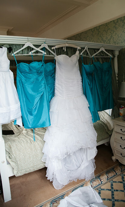 white organza mermaid dress and teal short bridesmaids dresses