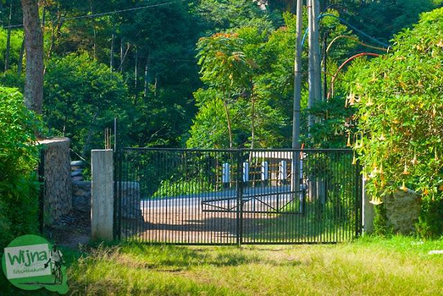 gerbang besi akses masuk ke Curug Bugbrug, Bandung Barat dari pinggir jalan raya kolonel masturi