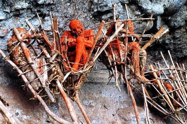 Dos penhascos de uma aldeia nas montanhas Morobe, os cadáveres carbonizados observam os transeuntes no pé da montanha.