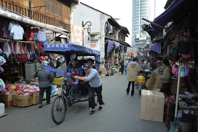 man pushing a bicycle rickshaw at Xiaoshan Street in Shaoxing, China
