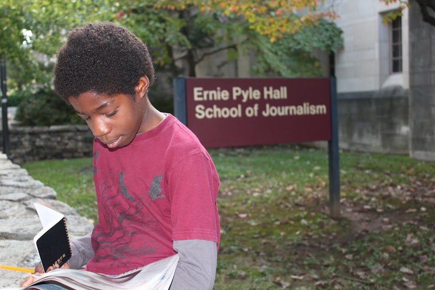 Ben reads a newspaper in front of Ernie Pyle Hall School of Journalism