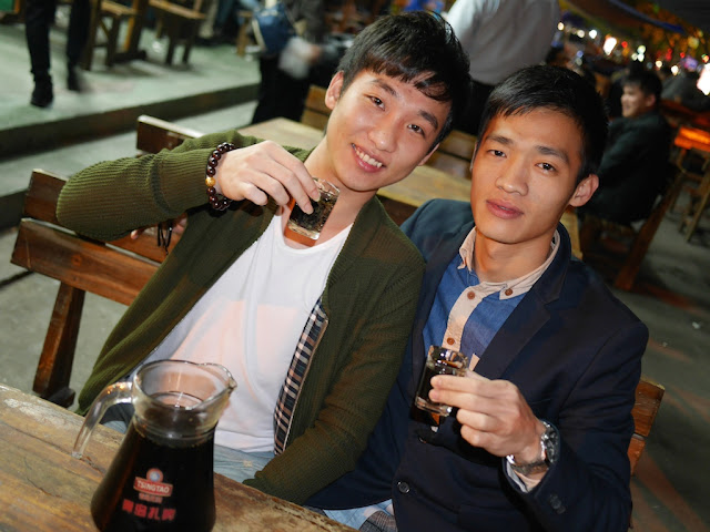 two young men holding shot glasses in Maoming, China