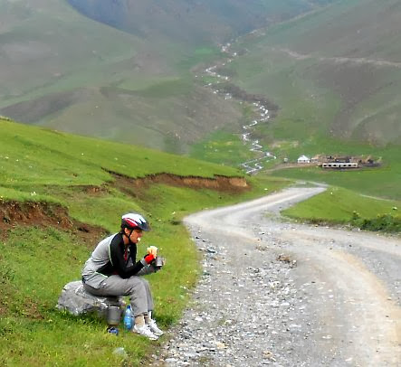 Pause mit Fahrradhelm bei der Auffahrt vom Tölök-Tal zum Kalmak-Ashu-Pass (3445 m), Kirgistan