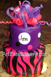 Girl's two tier purple, pink and black zebra stripe and polka dot custom designed fondant birthday cake with bow topper