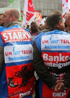 Demo mit Fahnen und Transparenten. Im Vordergrund zwei Demonstranten mit Umhangtransparenten: »UMfairTEILEN Reichtum besteuern, Banken enteignen.«.
