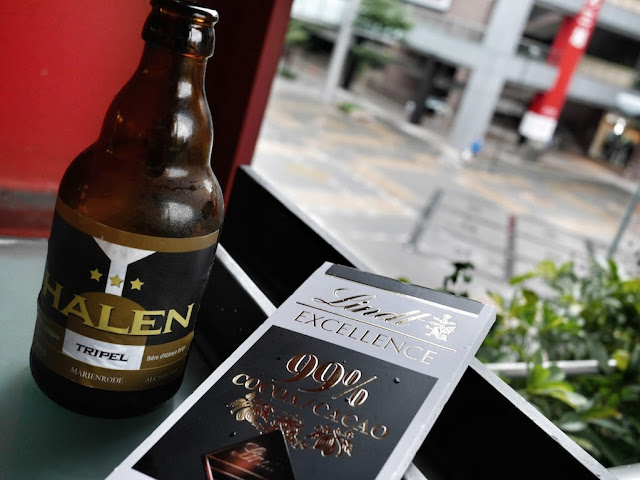 A bottle of Halen Tripel 9% alcohol beer and a bar of Lindt 99% cocoa chocolate