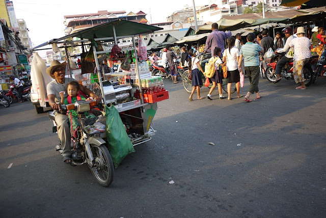 man with child driving a motorbike with a mobile drink cart in Phnom Penh