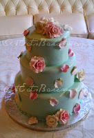 Three tier mint green fondant elegant romantic wedding cake with edible pink and ivory roses and petals with a touch of gold