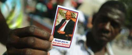 A Haitian man shows his loyalty to former President Jean-Bertrand Aristide. – Photo: Hector Retamal, AFP