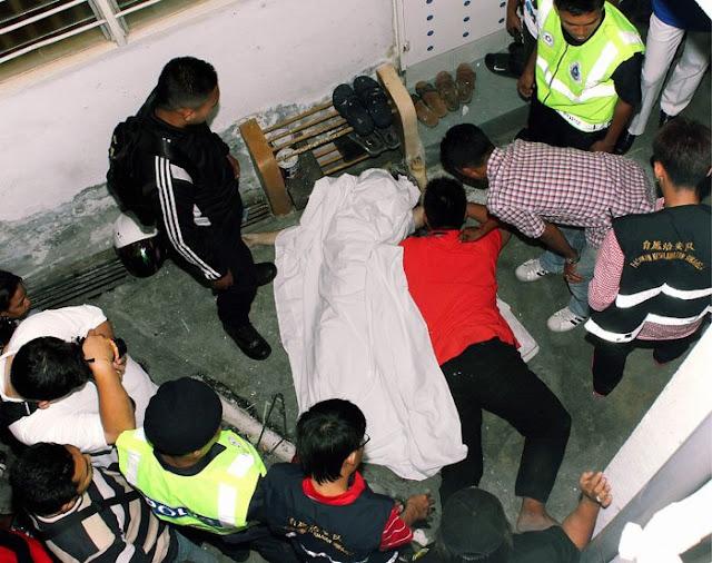 SEORANG lelaki (baju merah) terpaksa dipujuk hampir sejam oleh anggota polis selepas dia enggan melepaskan mayat teman wanitanya yang terjatuh dari tingkat 16 Flat Taman Utara, Batu Uban. Foto: Micheal Ong (25/01/2012)