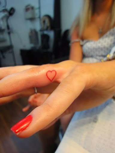 small red ink heart tattoos on finger