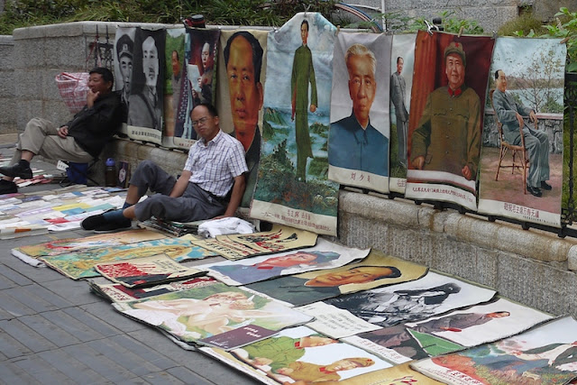 man sitting next to posters, many of Mao Zedong, for sale outside Tianxinge Antique City in Changsha, China