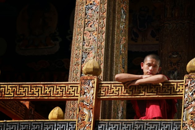 Buddhist Monk from the balcony of a temple in Punakha Dzong, Bhutan